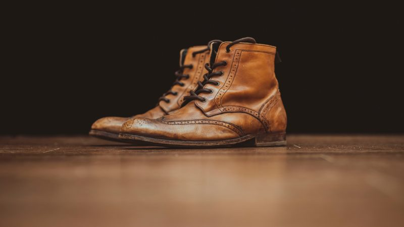 pair-of-brown-leather-booties-on-brown-surface